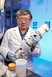 Chemist removes a sample of wood from chamber: Click here for full photo caption.