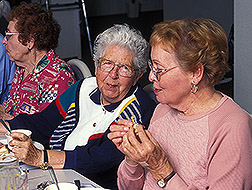 Three elderly women eating a meal.