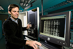 Geneticist loads an automated DNA sequencer for genetic analysis: Click here for full photo caption.