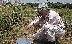 Brazilian soil scientist collects gas sample: Click here for full photo caption.