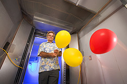 Retired chemist uses balloons to check airflow patterns of the air curtains positioned vertically on either side of the doorway: Click here for full photo caption.