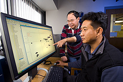Chemist (pointing) and postdoc view two-dimensional nuclear magnetic resonance data of a dissolved whole cell wall: Click here for full photo caption.
