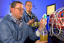 Microbiologist (left) and molecular biologist monitor bacterial growth and production of a biopolymer for use in plastics and other products: Click here for full photo caption.