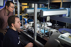 "Molecular biologist (left) and technician use the automated ""plasmid-based functional proteomic work cell"" that may help them develop yeast strains to improve ethanol production: Click here for full photo caption."