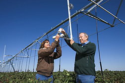 Agricultural engineers adjust the field of view for wireless infrared thermometers mounted on a center pivot irrigation system: Click here for full photo caption.