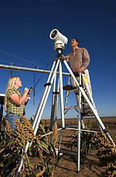 Agricultural engineer (on ladder) and hydrologic technician determine the water loss from a field by measuring the sensible heat flux with a large-aperture scintillometer: Click here for full photo caption.