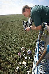 Technician, agricultural engineers, and soil scientist takes vertical images in the infrared and ordinary spectrums of cotton under water stress: Click here for full photo caption.