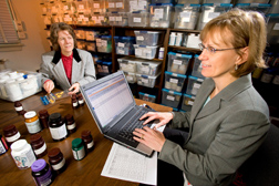 Chemist (right) logs in test sample ID numbers as nutritionist counts dietary supplement tablets for analysis of caffeine content: Click here for full photo caption.