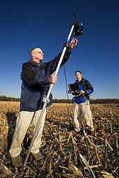 In a cornfield at Beltsville, Maryland, agronomist (left) and remote-sensing specialist use a portable spectroradiometer to measure reflectance of crop residues and soil: Click here for full photo caption.