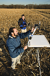 Soil scientist (left) and remote sensing specialist calibrate a portable spectroradiometer over a white panel prior to measuring the reflectance of the crop residues and soils in a cornfield: Click here for full photo caption.