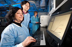 In efforts to develop new techniques to quickly and reliably identify pathogenic E. coli serogroups, microbiologist (left) and molecular biologist (center) view real-time PCR results from study samples as another microbiologist loads a thermal cycler with more samples for testing: Click here for full photo caption.