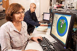 Agricultural engineer Susan O'Shaughnessy views an irrigation prescription map constructed from data collected by an ARS wireless sensor system. The map shows variable crop water needs. Next to her, agricultural engineer Joaquin Casanova tests his prototype TDR (time domain reflectometry) probe: Click here for photo caption.