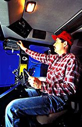 In the cab of a corn harvester technician checks readings on a digital yield monitor.