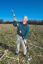 Scientist holds a probe to monitor soil moisture: Click here for full photo caption.