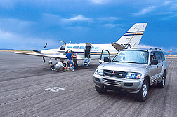 Several scientists load equipment on a twin-engine Cessna plane: Click here for full photo caption.