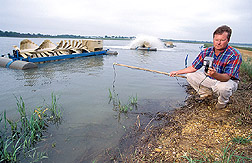 Extension agent takes an oxygen reading from a catfish pond: Click here for full photo caption.