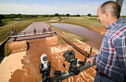 From an observation platform overlooking a test dam, Greg Hanson records the test for use in computer modeling. Link to photo information