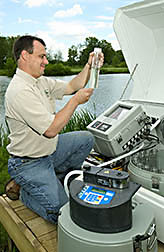 Agricultural engineer examines discharge water from a turfgrass system in central Ohio: Click here for full photo caption.