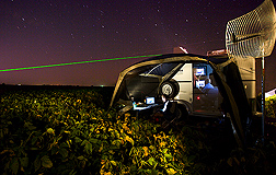 A LiDAR laser is seen tracking across an Iowa landscape to measure the particulate plume at night: Click here for full photo caption.