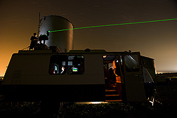 A laser beam is positioned to track the particulate plume from a swine facility: Click here for full photo caption.