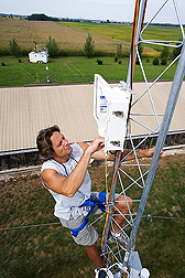 Soil scientist climbs a 30-meter tower to inspect air-sampling equipment: Click here for full photo caption.