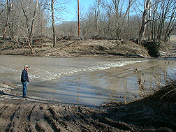 A cooperator with Missouri Corn Growers surveys a section of Long Branch Creek in Missouri: Click here for full photo caption.