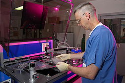 "In preparation for sequencing Leptospira's genome, technician loads a 96-well plate into a machine known as a ""colony picker."": Click here for full photo caption."