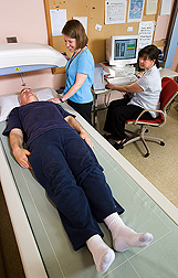 Two nutritionists perform a DXA scan on a volunteer. Link to photo information