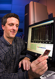 The chip that the geneticist is holding allows him to evaluate more than 380 pigs for genetic variations at 6 different regions of the genome: Click here for full photo caption.