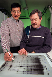 Geneticist (left) and Michigan State University professor examine genetic marker results: Click here for full photo caption.