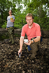 USDA Forest Service ecologist uses a global positioning system to determine an area's exact location while an ARS soil scientist measures soil moisture at the location: Click here for full photo caption.