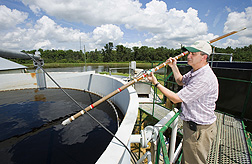 Using a deep sampling probe, ARS soil scientist inspects the amount of calcium phosphate produced in a phosphorus-separation module that is part of the new system: Click here for full photo caption.
