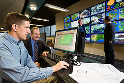"ARS hydrologist (far left) and Penn State University climatologist examine regional data they are using to develop a Web-based ""fertilizer forecast."" The program will use a range of weather variables, including the type of meteorological data Penn State associate professor and ARS soil scientist (far right) are studying in the background: Click here for full photo caption."
