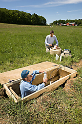 Hydrologist (right) and laboratory worker collect runoff water samples from a hillslope trench that is being used to monitor lateral subsurface flow pathways during and after storms: Click here for full photo caption.