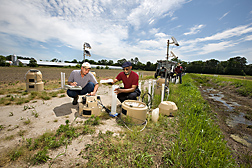 "ARS soil scientist (left) and UMES associate professor collect samples of groundwater before and after it is filtered through an underground ""curtain"" of gypsum: Click here for full photo caption."