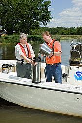 ARS agronomist (left) and soil scientist collect a water sample on the Choptank River for pesticide and nutrient analyses: Click here for full photo caption.