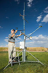 Agricultural engineer checks instruments on a weather station that predicts water consumption through soil surface evaporation and transpiration through plant leaves: Click here for full photo caption.