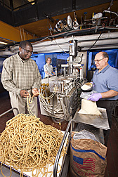 Food technologist (left) inspects extruded instant corn-soy blend before milling and packaging while engineering technician (right) scoops up a corn-soy blend intended for extrusion. In the background, chemist monitors the control console: Click here for full photo caption.