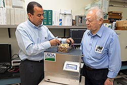ARS engineers Samir Trabelsi (left) and Stuart O. Nelson (retired) test a sample of peanuts for moisture content using the new moisture-sensing meter they invented in Athens, Georgia.