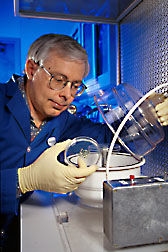 Biological research technician places barley tissue into the vacuum pressure chamber of a gene-delivery device. Click here for full photo caption.
