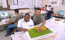 Geographic information specialist and research assistant reviewing data maps and charts: Click here for full photo caption.
