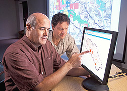 Researchers Ron Bingner (left) and Eddy Langendoen study data generated by a model. Click the image for additional information about it.