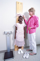 Clinical coordinator measures height and weight of a study participant: Click here for full photo caption.