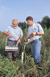 Scientists Lowrance (L) and Vellidis pump water from sampling well at edge of restored riparian buffer. Click the image for additional information about it.