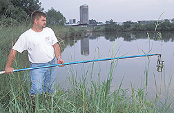 Engineer collects water from a farm pond: Click here for full photo caption.