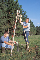 Engineer and technician take a deep soil sample from the edge of a buffer system: Click here for full photo caption.