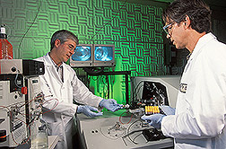 Chemist Chris Silva (left) and research leader J. Mark Carter load samples for analysis. Link to photo information