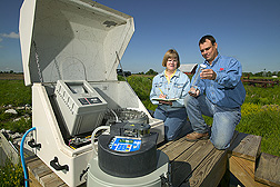 Technician and agricultural engineer take notes on a sample of water: Click here for full photo caption.