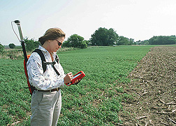 Hydrologist uses a global positioning system to record the status of a filter strip planting: Click here for full photo caption.