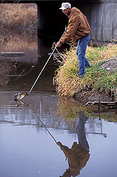 Technician collects a sample from a watershed in Ames, Iowa: Click here for full photo caption.